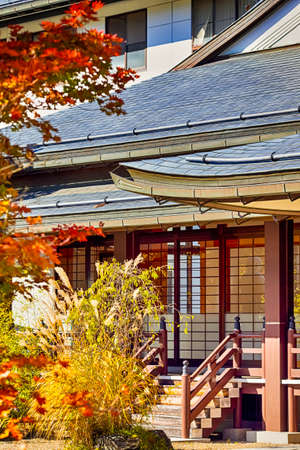 Japanese Heritage. Seasonal Red Maples in Front of The Monastery Gates on Sacred Mount Koyasan in Japan.Vertical Image Composition Editorial