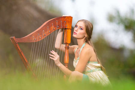 Slim Caucasian Woman in Long Decorated Dress Posing with Harp Against Ivy Wall. Vertical Shoot