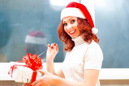 Seasonal Holidays Ideas. Portrait of Happy Smiling Caucasian Santa Helper Girl Unwrapping Christmas Gift Box. Horizontal Image