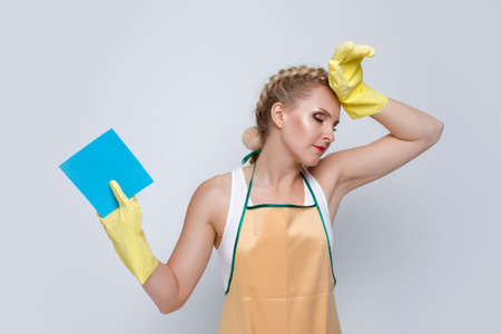 Household Ideas. Portrait of Tired and Exhausted Caucasian Female With Rubber Sponge Posing With Lifted Hands Against White. Horizontal Image Zdjęcie Seryjne