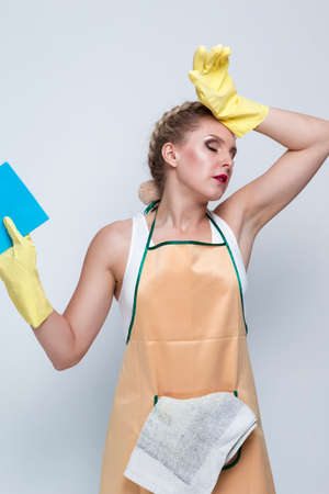 Household Concepts. Portrait of Frustrated Caucasian Female With Rubber Sponge Posing With Lifted Hands Against White. Vertical Orientation Zdjęcie Seryjne