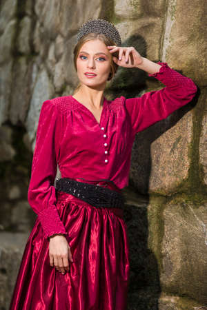 Confident Caucasian Girl With Silver Tiara Posing in Red Dress with Lifted Hand Against Old Building. Horizontal image Composition