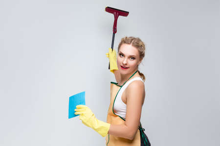 Household Cleaning Ideas. Caucasian Female Holding Rubber Scraper Swab With Rubber Gloves and Doing Cleaning Against White.