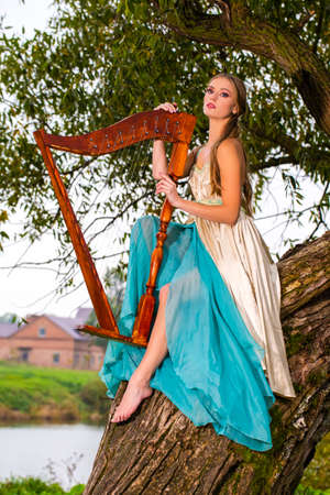Portrait of Caucasian Blond Woman in Long Dress Playing the Harp on Tree Branch in Park Outdoors.Vertical Image