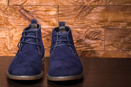 Footwear Ideas. Closeup of Pair of Mens Blue Suede Semi-Brogue Boots Against Wooden Background Indoors.Horizontal Image Composition Reklamní fotografie