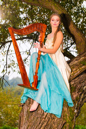 Portrait of beautiful caucasian blond woman in long dress playing the harp in park outdoors.Vertical Image