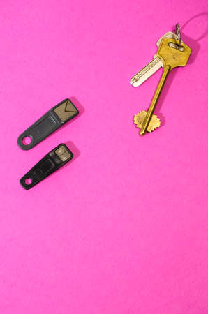Home Concepts. Bunch of Traditional Metal House Keys Against Pair of Electronic Chip Keys Together Over Colorful Background.Vertical Composition