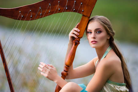 Portrait of Relaxing Sensual Harpist Woman in Light Dress Playing Music in Park Outdoor.Horizontal Image