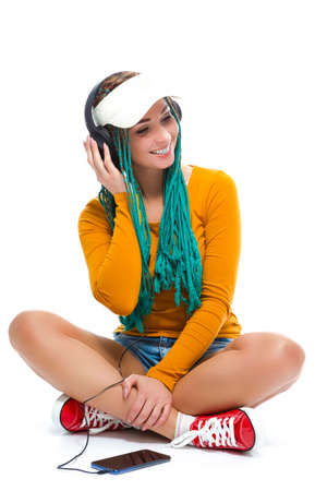 Happy Smiling Caucasian Female with African American Dreadlocks Listening Music In Wireless Headphones With Cellphone On Floor. Vertical Composition Фото со стока