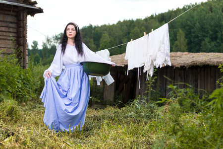 Portrait of Brunette Caucasian Girl With Basin of Laundry Against Hanged Linen on Rope Behind In Countryside Environment. Horizontal Image