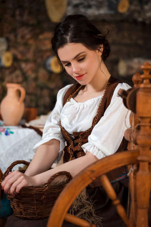 Relaxing Caucasian Brunette Woman Posing With Wooden Wicker Basket in Retro Dress In Village Environment. Vertical Image