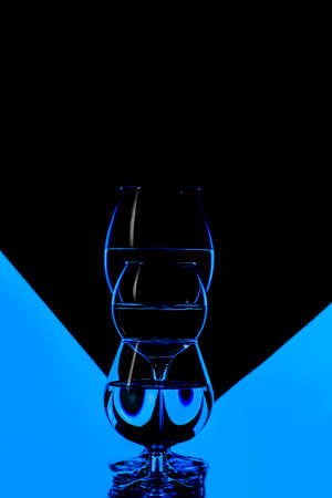 Three Different Glass Cups Placed in One Line Against Black And Blue Background. Vertical Composition Foto de archivo