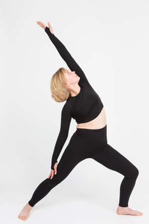 Portrait of Mature Caucasian Woman Practicing Yoga Asana Pose In Professional Sport Outfit Over Isolated White Background. Vertical Image