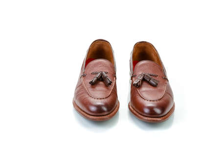 Footwear Concepts. Pair of Formal Stylish Brown Pebble Grain Tassel Loafer Shoes On White Reflective Surface. Horizontal image