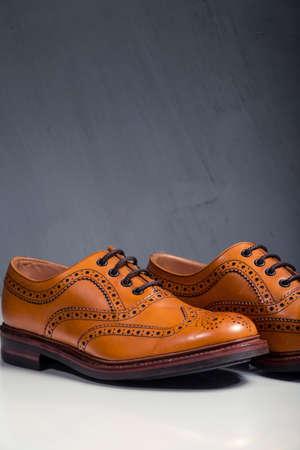 Male Footwear Ideas. Pair of Full Broggued Tan Leather Oxfords Broggued Shoes Against Gray Background. Vertical Image Orientation Zdjęcie Seryjne