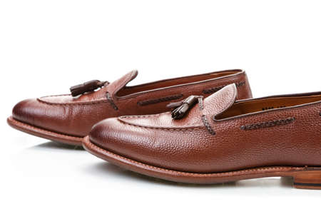 Footwear Concepts. Pair of Formal Stylish Brown Pebble Grain Tassel Loafer Shoes On White Reflective Surface. Horizontal Shot