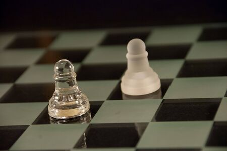 Glass chess board with white and black pieces ready to face off and do battle.