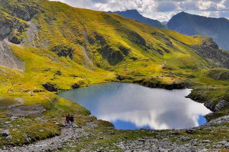 Tourists hiking and camping near mountain lake Stock Photo