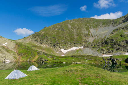 oriented: Mountain landscape with camping tents near the lake.