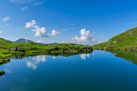 Beautiful view of high mountain lake with sky mirrored in water. Stock Photo