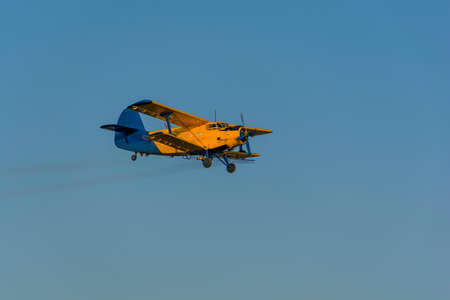 Crop duster spraying crops from the air in the morning light