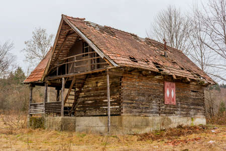 the collapsing: Old rural abandoned wooden collapsing house against cloudy sky in autumn season Stock Photo