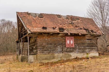 dwell: Old rural abandoned wooden collapsing house against cloudy sky in autumn season Stock Photo