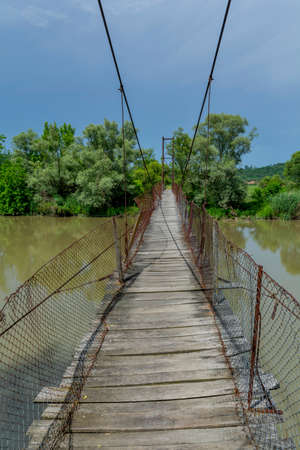steel cable: Old steel cable and wooden footbridge across river. Wooden suspension bridge.
