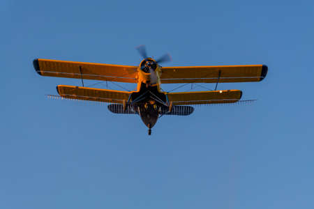 aircrew: Crop duster spraying crops from the air in the morning light. Below view