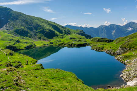 Mountain lake with crystal clear water. Landscape from Capra Lake in Romania and Fagaras mountains in the summer. Stock Photo