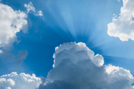 Sun rays through the clouds. Blue sky with sun rays. Stock Photo