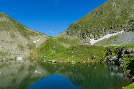 Beautiful view of high mountain lake. Landscape from Capra Lake in Romania and Fagaras mountains in the summer. Stock Photo