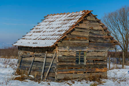 Landscape of old abandoned farm house covered with snow in a frosty winter. Old broken house in winter season. Stock Photo