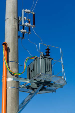 New distribution transformer on concrete power pole with external electric separator against the blue sky. Stock Photo