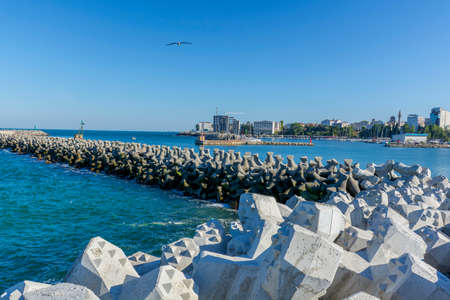 tetra: Bay view of the port town of Tomis, Constanta.  Tetra-pods or concrete breakwater blocks at Tomis, Constanta harbur. Sea wall for protect the beach.  Breakwaters concrete tetra-pods.
