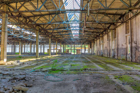 Abandoned large factory industrial interior. Inside the ruins of an old factory in Romania of a Communist Era. Step inside of abandoned old factory in eastern Europe. Stock Photo