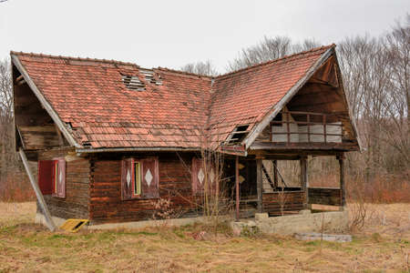 Old rural abandoned wooden collapsing house against cloudy sky in autumn season 版權商用圖片