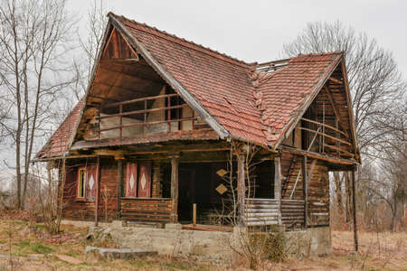 Old rural abandoned wooden collapsing house against cloudy sky in autumn season Imagens