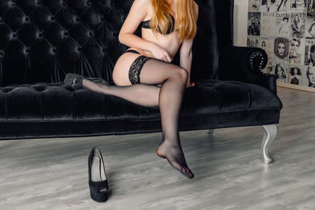 ankles sexy: Beautiful young woman sitting on sofa with one leg in high heel shoe and stockings