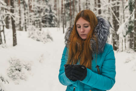 Girl heated with a cup of tea or coffee in the winter forest. Hot mulled wine in cup.