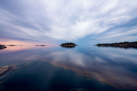 morning blue hour: Reflections of a cloudy sky on the lake. Mirror summer lake. Ladoga lake in Karelia.