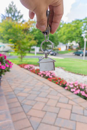 close up a house shape key chain in front of a beautiful house Stock Photo