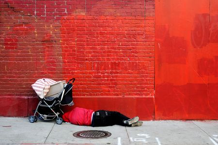 itinerant: Man sleeping in front of red wall Stock Photo