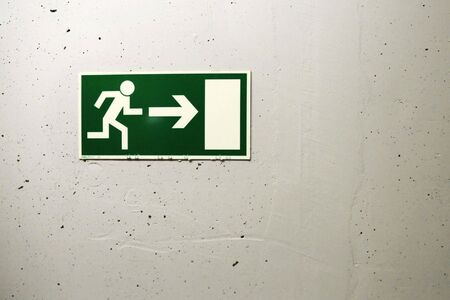 Exit sign hanging on a concrete wall  Stock Photo