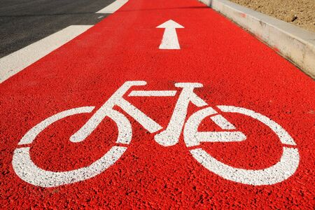 Red bicycle lane with white bicycle sign