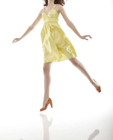 Woman jumping in yellow dress