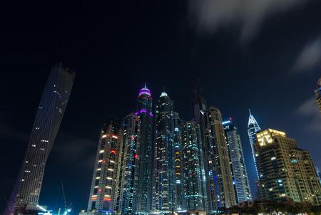 mag: dubai marina city lights lit up at night with famous landmark buildings