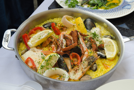 marisco: seafood paella being cooked in a silver frying pan