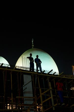 untied: construction workers working in the middle of the night in deira, dubai untied arab emirates