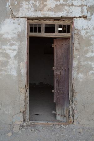 al: Traditional weathered wooden door frame, Old Ras Al Khaimah abandoned ghost town, Al Jazirah Al Hamra